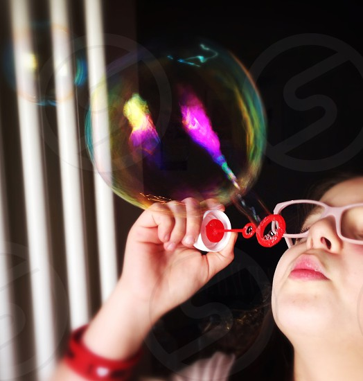girl making bubbles photo