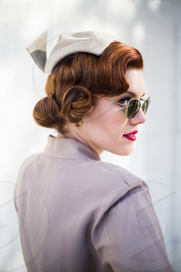 Vintage pin-up girl sunglasses red hair blue eyes hat dress. Retro fashion. photo