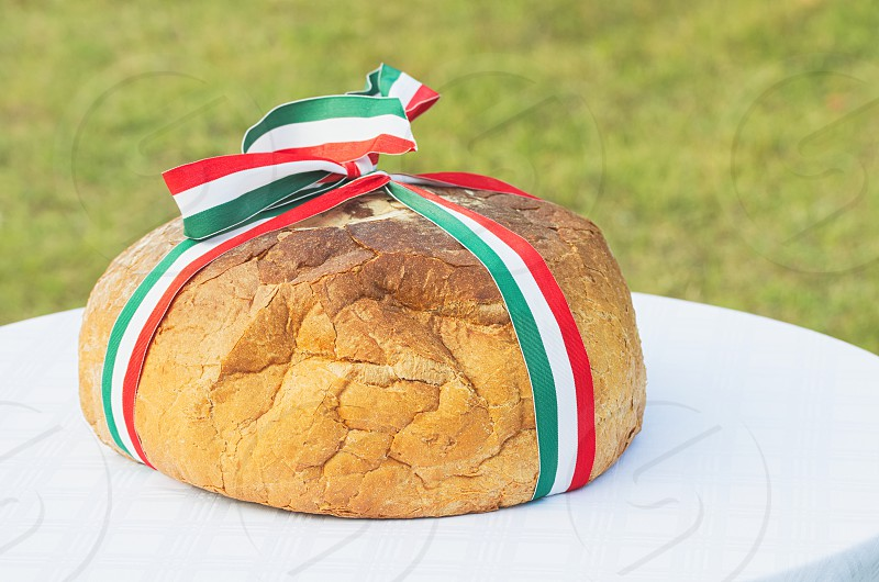 Whole Bread with Hungarian Tricolor Ribbon on a White Cloth Outdoors photo