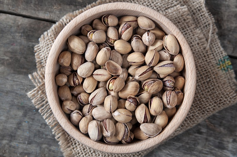 Cracked and Dried Pistachio Nuts In A Wooden Bowl photo