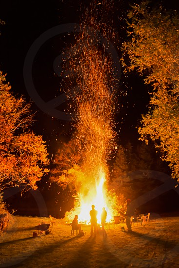 5 person besides bonfire during night photo