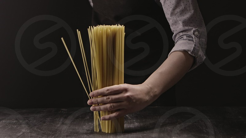 Raw uncooked spaghetti falling in slow motion from cook's hand on a black background. Slow motion Full HD video 240fps 1080p. Concept of italian food and cooking dinner. photo
