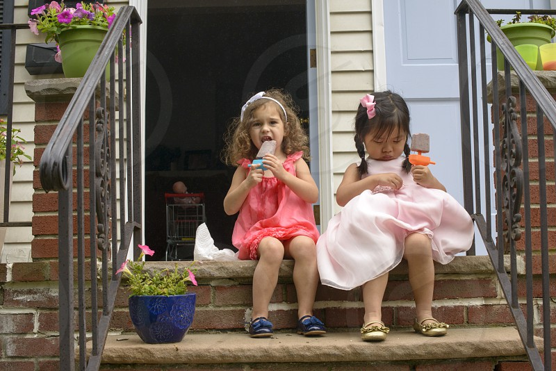 girl in pink halter dress eating popsicle while sitting beside girl in light pink dress photo