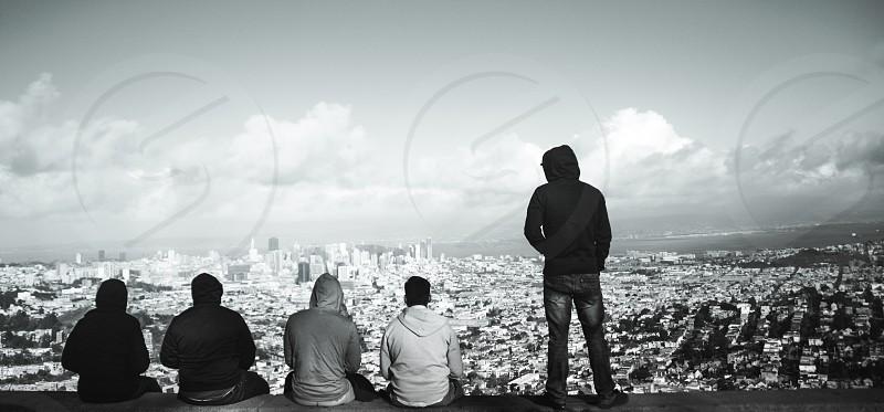 five men wearing hoodies looking on city view photo