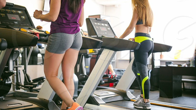 young woman is engaged fitness in gym. Performs cardio load on treadmill running and walking with acceleration. sport fit lifestyle technology and people concept photo