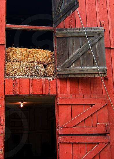 Portion of a barn showing hay bales in a hayloft above in the door. photo