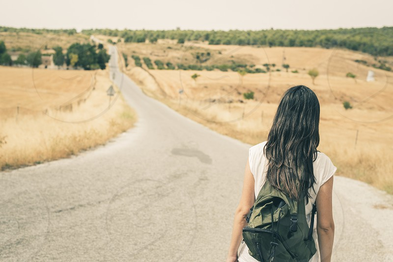Woman with backpack walking on the road photo
