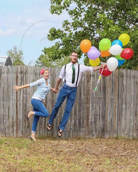 Couple balloons jump photo