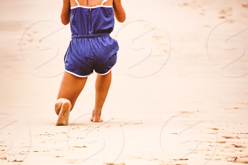 lunges during a beach walk low section young woman wearing a shorts jumpsuit healthy lifestyle fit and active photo