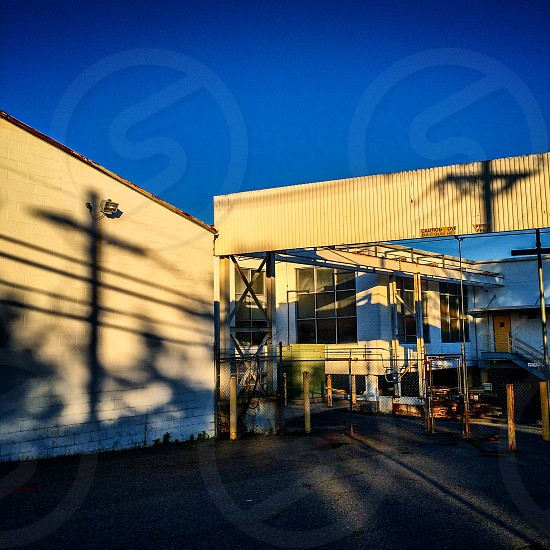 Shadows of utility poles against a factory. photo