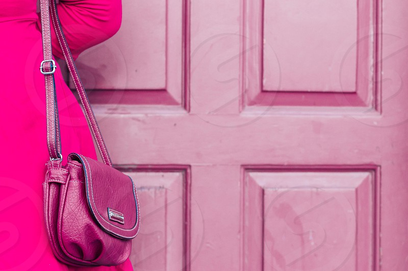 woman in pink dress with purple sling bag standing in front of pink wooden panel door photo