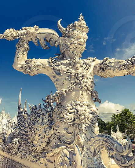 Outdoor day vertical portrait colour Wat Rong Khun The White Temple Chiang Rai Thailand Thai Kingdom of Thailand travel tourism tourist wanderlust summer summertime temple Buddhist Buddhism spiritual pure holy dragon monster carved ornate elaborate art modern sculpture sculpted east eastern hands silver mirror mosaic magical stretch stretched warrior attack mythical skulls photo