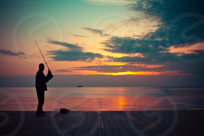 silhouette of person fishing in body of water during golden hour photo