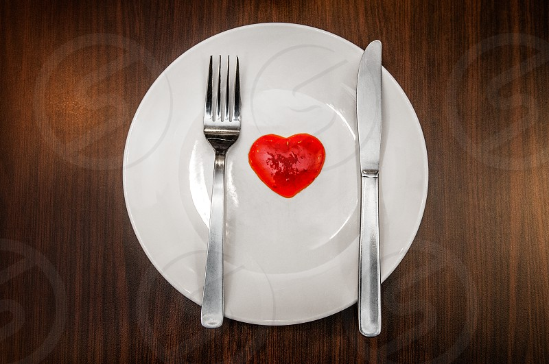 White plate with chili sauce fork and knife on rustic wooden table. photo