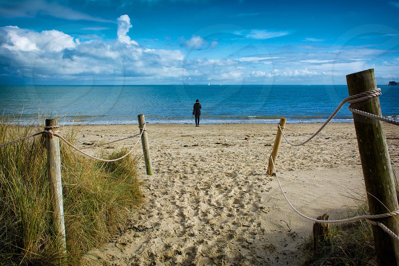 a human on the sand of the shore line during daytime photo