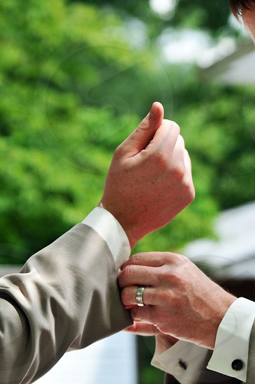 Close-up of hands attaching cufflinks to a suit photo