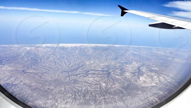 Plane flying land ocean and sky blend together photo