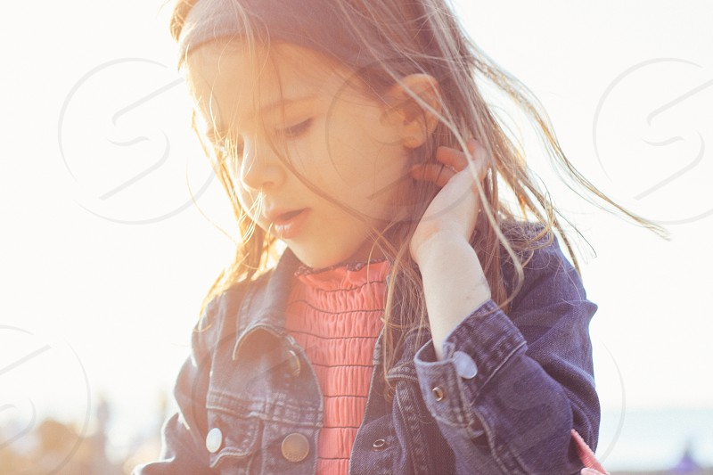 girl in blue denim jacket standing during daytime photo