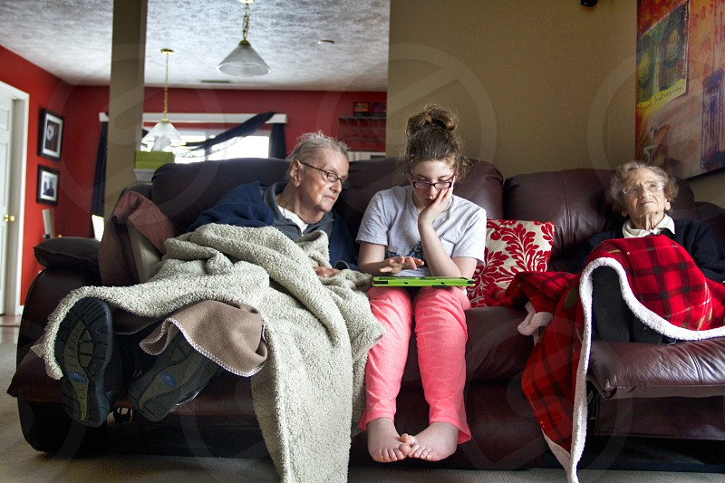 Grandfather and granddaughter spending the morning using the tablet together.  photo
