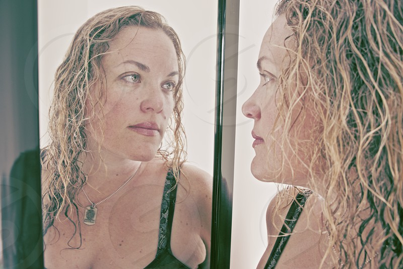 woman looking into her own reflection in deep self examination photo