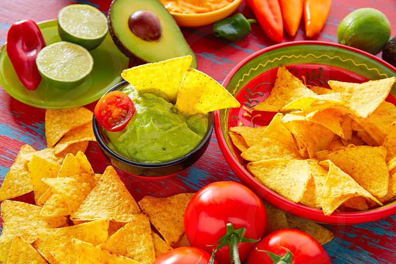 Mexican food nachos and guacamole with chili peppers and sauces photo