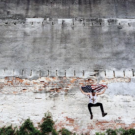 man jumping holding american flag photo