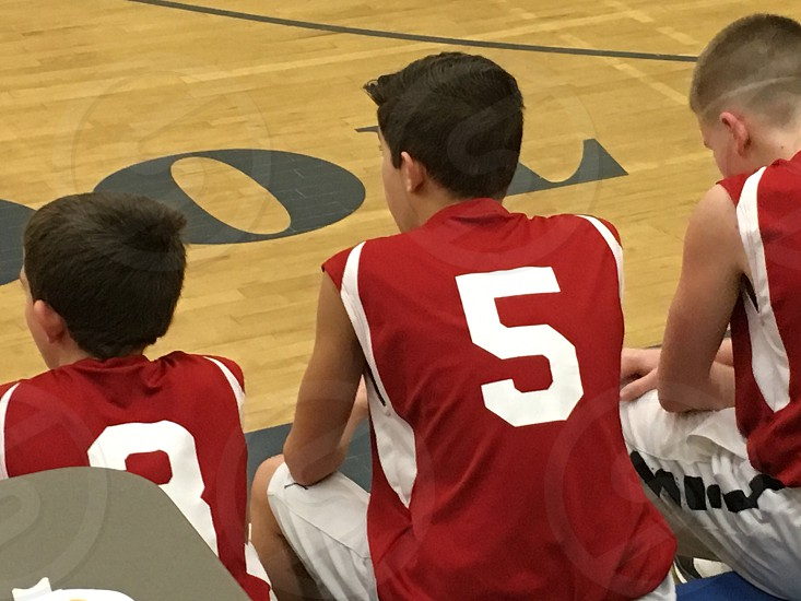 boy's sitting beside basketball court in red and white uniforms photo