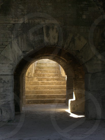 Entrance from lower level of Roman amphitheater to steps leading to upper level tunnel shadows contrast structure building sport facility ancient photo