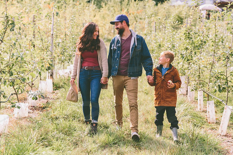 A young family walking together through an orchard. photo