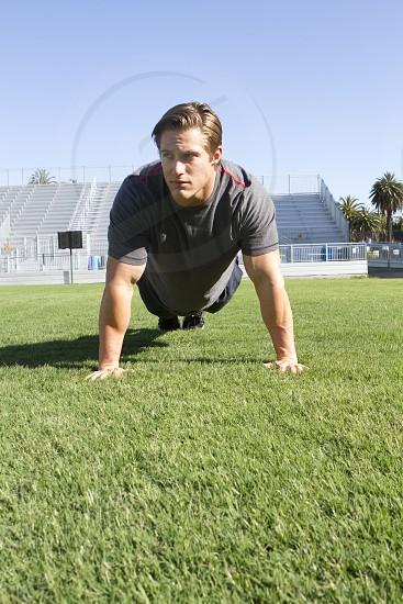 man in gray crew neck t-shirt doing push ups on green grass photo