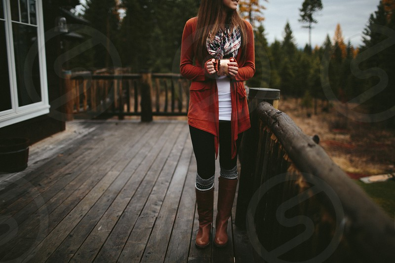 woman in red cardigan and brown boots holding a mug of coffee on a wooden deck photo