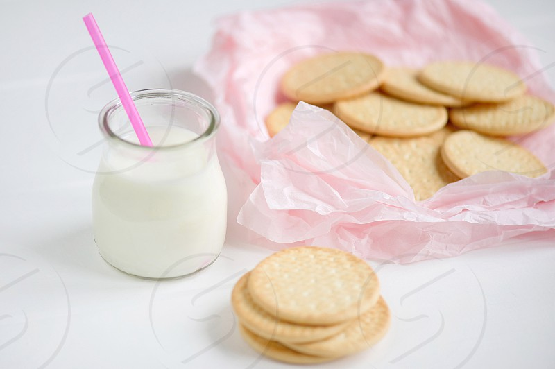 baked cookies near clear drinking glass with milk photo