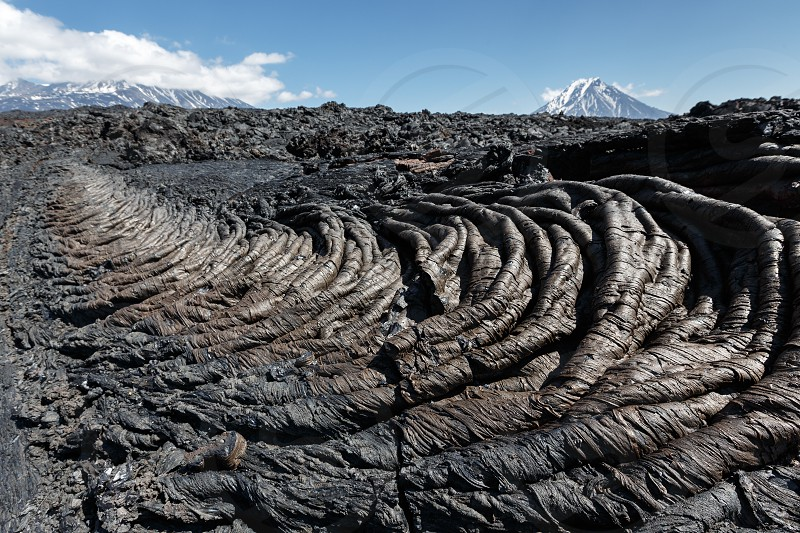 Volcanic landscape of Kamchatka Region: beautiful view of lava field volcanic eruption active Plosky Tolbachik Volcano on a sunny day. Eurasia Russian Far East Kamchatka Peninsula Klyuchevskaya Group of Volcanoes. photo