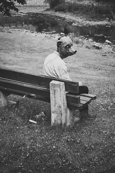 black and white photo of man with bear mask sitting on bench photo