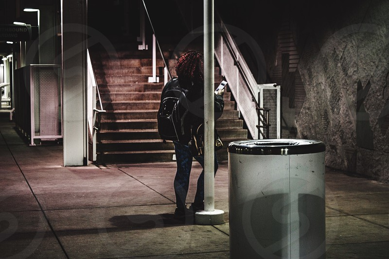 Denver Colorado waiting train station woman one person night city lights city nights steps red hair using phone reading backpack fashion street photography mile high city alone time traveler travel  photo