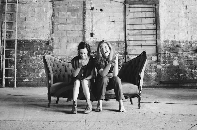 Black and white photo two women smiling sitting on an antique couch photo