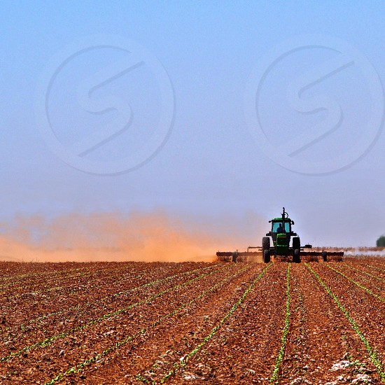 A West Texas farmer plows a dusty dry field on a sweltering summer afternoon.  photo