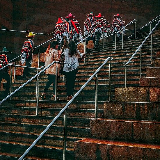 two woman wearing cardigans walking on stairs near people wearing mexican hat during daytime photo
