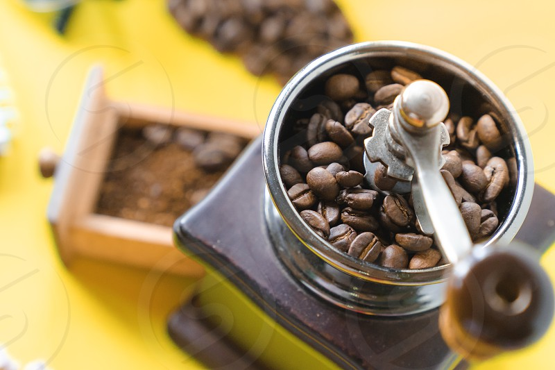 close up top view selective coffee beans and grinded coffee bean in vintage wooden coffee grinder on yellow background photo