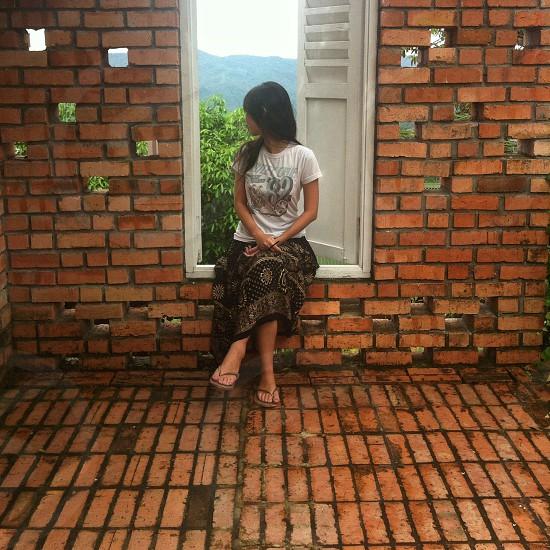 woman sitting in white wooden door photo