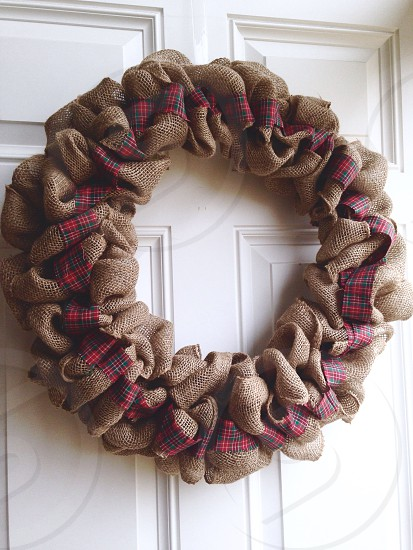 brown and red fabric wreath on white wooden door photo