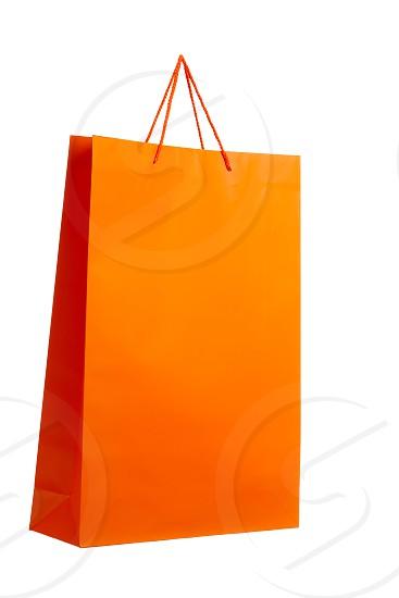 Orange paper bag isolated on white. Diagonal angle. photo