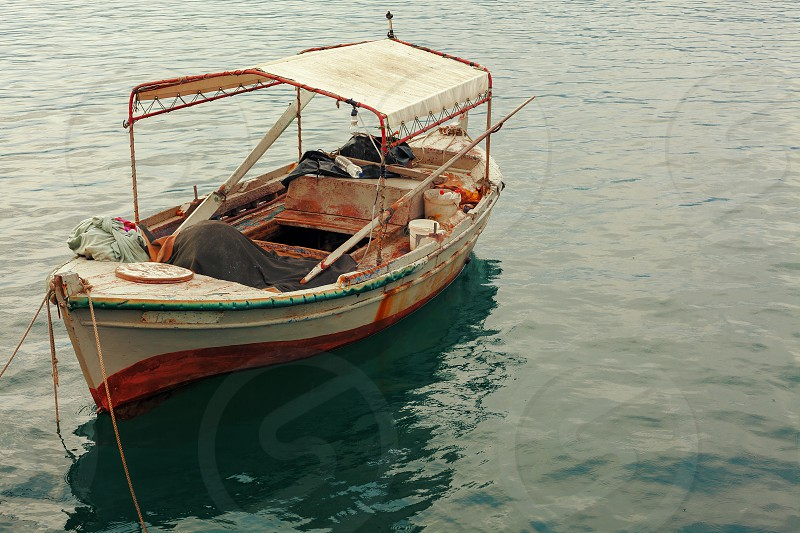 One old fishing boat with nets paddles and other equipment in sea water. photo
