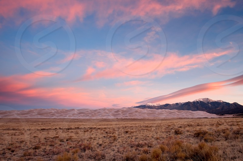 Coral colored sky and sand dunes greet sunrise in Great Sand Dunes National Park and Preserve in the San Luis Valley near Alamosa Colorado.  photo