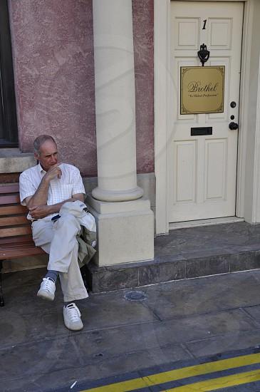 man sitting on bench chair photo