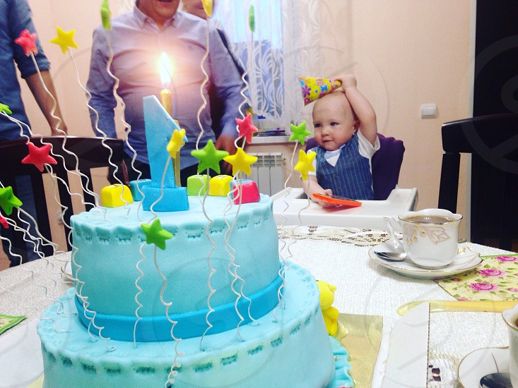 baby wearing blue waistcoat sitting on highchair facing blue fondant cake with 1 cake topper photo