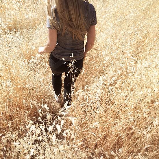 woman in grey shirt walking down grassy hill photo