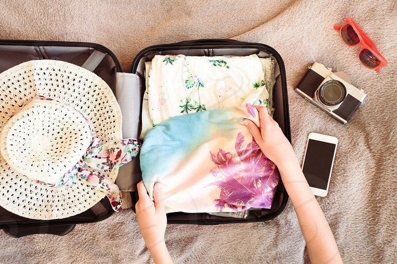 Time for summer vacation. Suitcase with packed summer clothes a camera a hat and sunglasses photo
