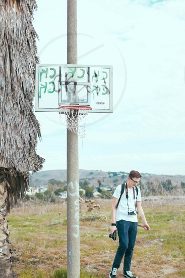 person with camera near basketball hoop photo