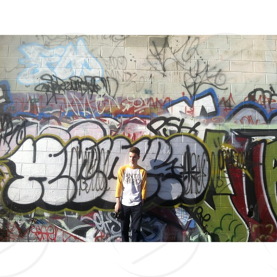 man in yellow and white round neck long sleeved shirt leaning on wall full of graffiti photo